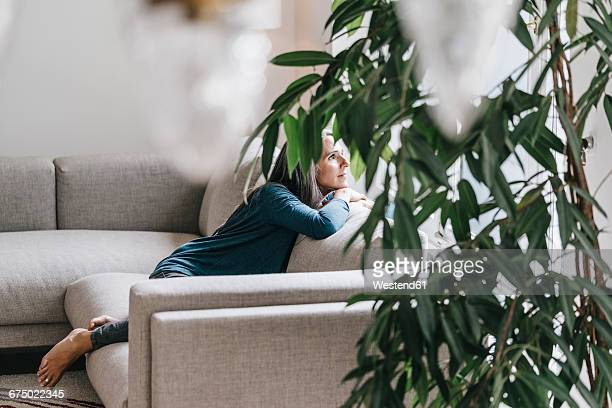 Woman sitting on the couch looking through window
