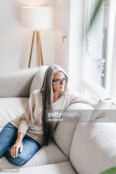 Woman sitting on the couch reading book