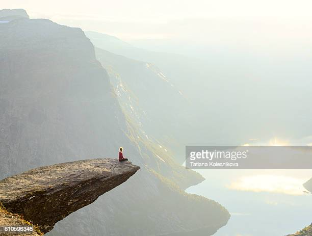 woman sitting on the edge of a cliff - norwegen stock-fotos und bilder