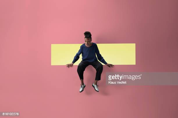Woman sitting on the edge of rectangular opening in coloured wall and looking down
