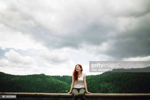 Woman sitting on the fence  at view point