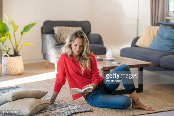 woman sitting on the floor at home reading book - donne bionde scalze foto e immagini stock