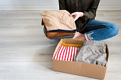 woman folding packing clothes into cardboard