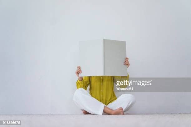 woman sitting on the floor hiding her face behind an oversized book - verdecktes gesicht stock-fotos und bilder