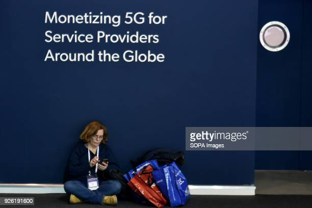 A woman sitting on the floor resting during their visit to the Mobile World Congress in Barcelona The Mobile World Congress 2018 is being hosted in...