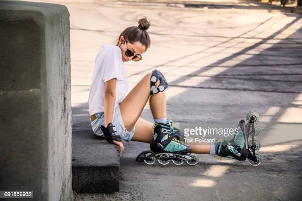 Woman sitting on the floor wearing inline skates in an industrial area - Germany, Bavaria, Wertheim