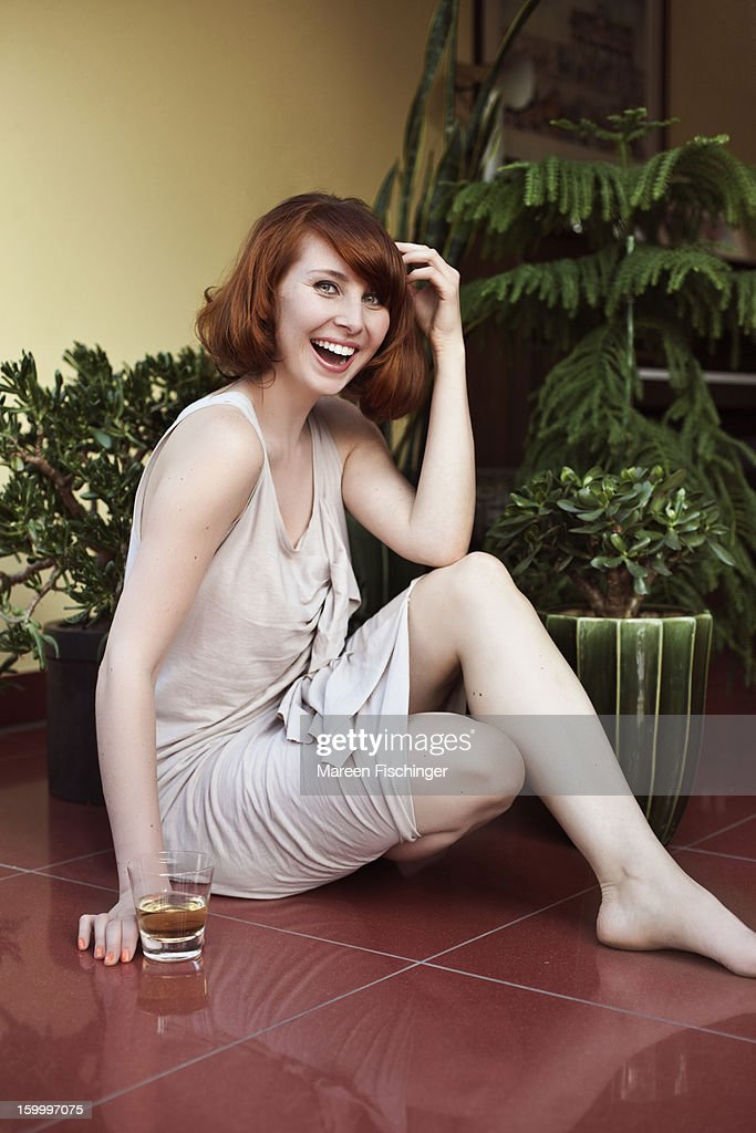Woman sitting on the floor with a drink, laughing : Bildbanksbilder