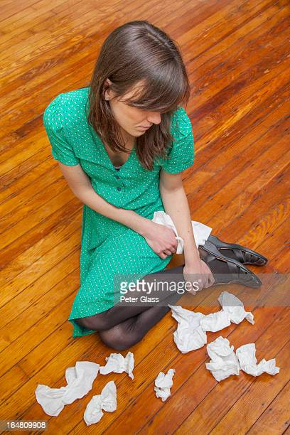 Woman sitting on the floor with tissues
