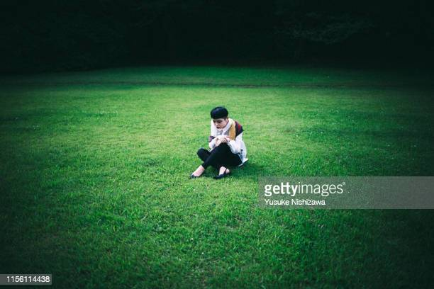 woman sitting on the grass. - yusuke nishizawa stock pictures, royalty-free photos & images