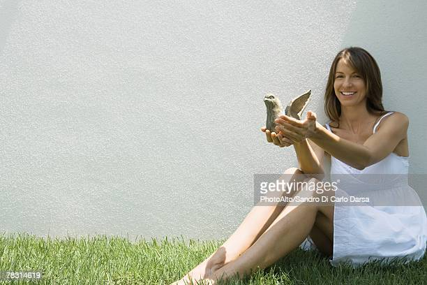Woman sitting on the ground holding wooden bird, smiling at camera