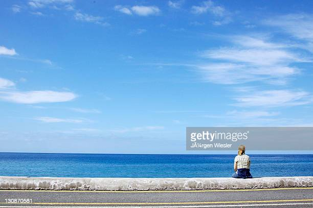 Woman sitting on the pier in La Puntilla, La Gomera, Canary Islands, Spain, Europe