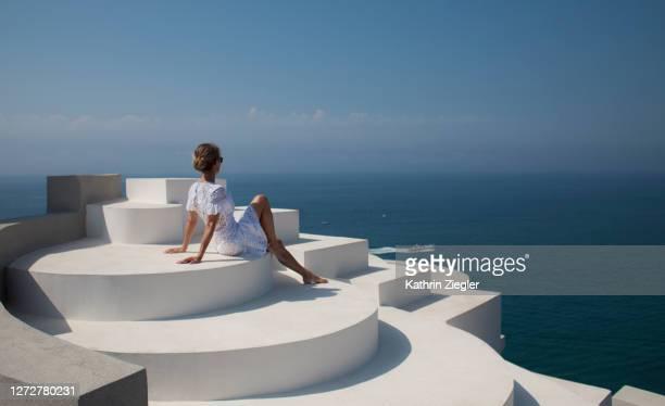 woman sitting on the rooftop of beautiful postmodern building, enjoying the sea view - weißes kleid stock-fotos und bilder