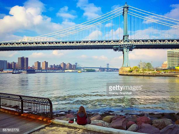 A woman sitting on the shore of the East River looking at the Manhattan Bridge