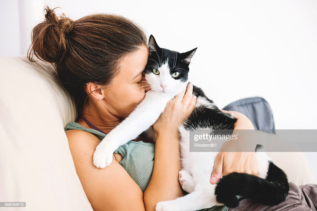 Woman sitting on the sofa hugging her cat : Stock Photo