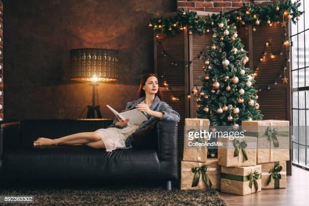 新年モミの近くのソファに座っている女性