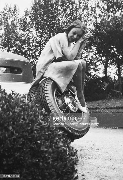 Woman sitting on the spare wheel of a car, in a garden, by Zoltan Glass. Woman sitting on the spare wheel of a car, in a garden. Photograph taken by...