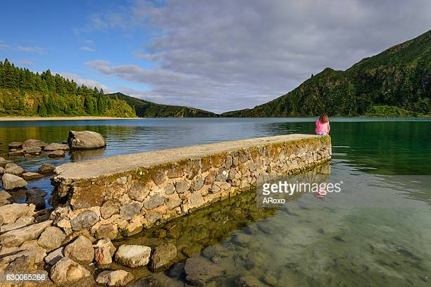 Woman sitting on the stone pier enjoying the beauty of the lake.