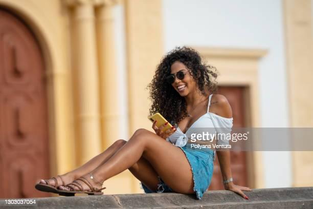 woman sitting on the wall talking on video call - sentar se imagens e fotografias de stock