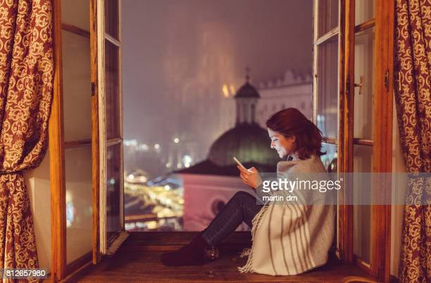 Woman sitting on the window sill and texting