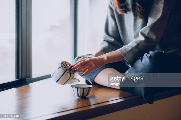 woman sitting on the windowsill and pouring a cup of tea - cerimónia imagens e fotografias de stock
