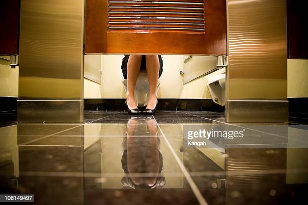 woman sitting on toilet - public restroom stock pictures, royalty-free photos & images