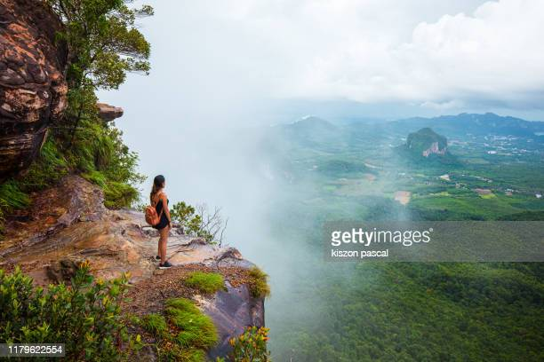 woman sitting on top of a mountain and looking at the view during a rainy day . - rainy season stock pictures, royalty-free photos & images