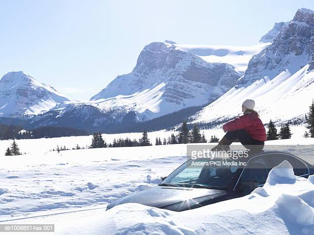 Woman sitting on top of car