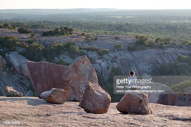 woman sitting on top of enchanted rock - austin texas stock photos and pictures