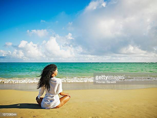 Woman sitting on tropical beach looking out