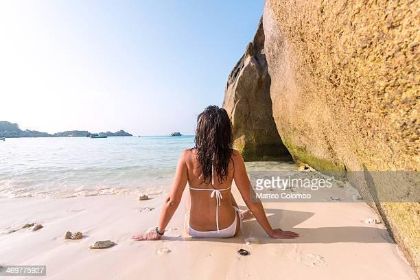 Woman sitting on tropical beach, Thailand