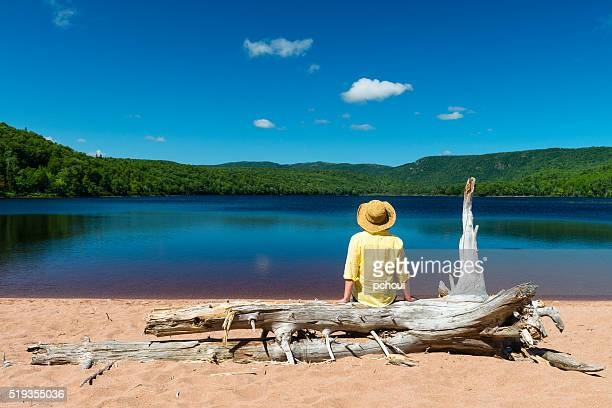 Woman sitting on trunk tree and looking at beautiful lake