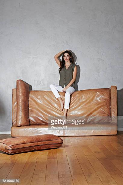 Woman sitting on upset leather couch