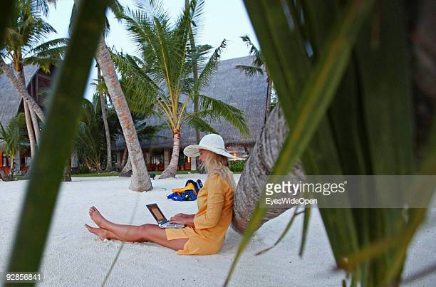 Woman sitting on Villingili beach working with a notebook and mobile phone surfing in the internet The island is owned by the luxurious ShangriLa's...