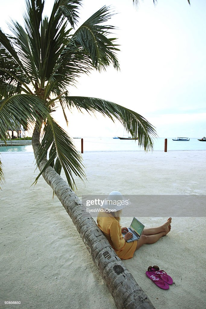 Woman sitting on Villingili beach, working with a notebook and mobile phone, surfing the internet. The island is owned by the luxurious Shangri-La's Villingili Resort and Spa Hotel on September 27, 2009 in Male, Maldives.The maldive islands consist of around 1100 islands and 400,000 inhabitants spread on 220 islands. Till 2008, between 30 years reign of Maumoon Abdul it was not allowed for tourists to visit local islands without special permission. Now from Villingili Island, tours are possible to visit the local islands of Addu Atoll.