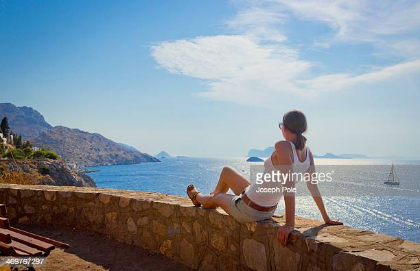 woman sitting on wall at sunset, greece - hydra greece stock photos and pictures