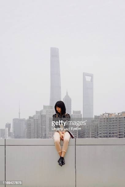 woman sitting on wall in city against buildings and sky - liu he stock pictures, royalty-free photos & images