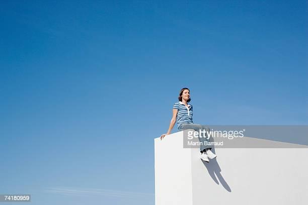Femme assise sur un mur à l'extérieur avec ciel bleu