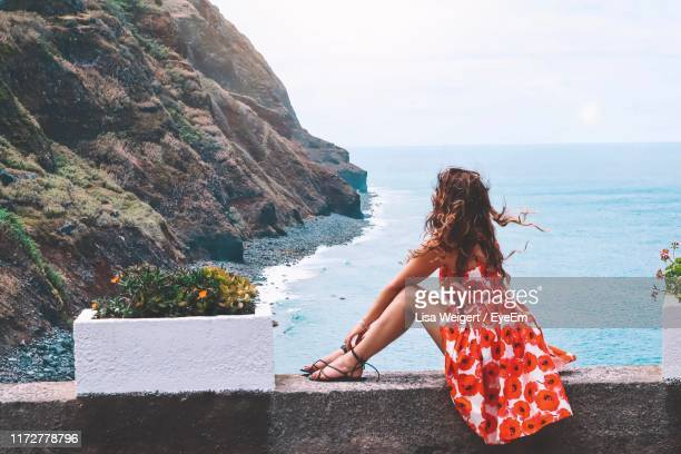 woman sitting on wall over sea against sky - ilha da madeira imagens e fotografias de stock