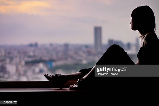 Woman sitting on window ledge looking out at city