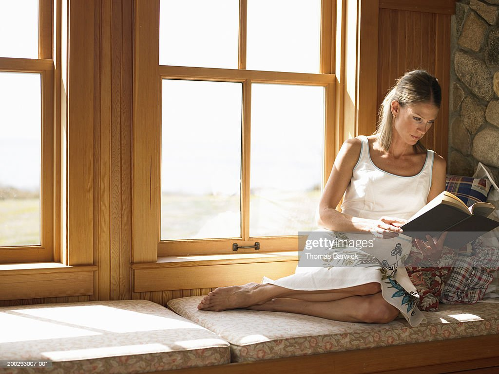 Woman Sitting On Window Seat Reading Book High Res Stock