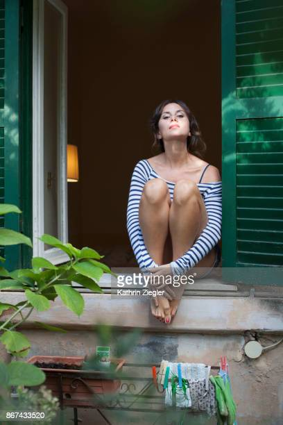 Woman sitting on windowsill as seen from the garden