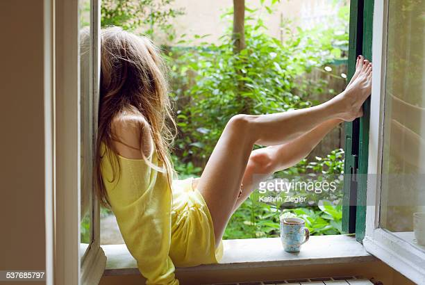 Woman sitting on windowsill with cup of tea