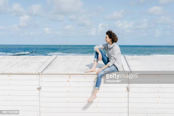 Woman sitting on wooden box on the beach
