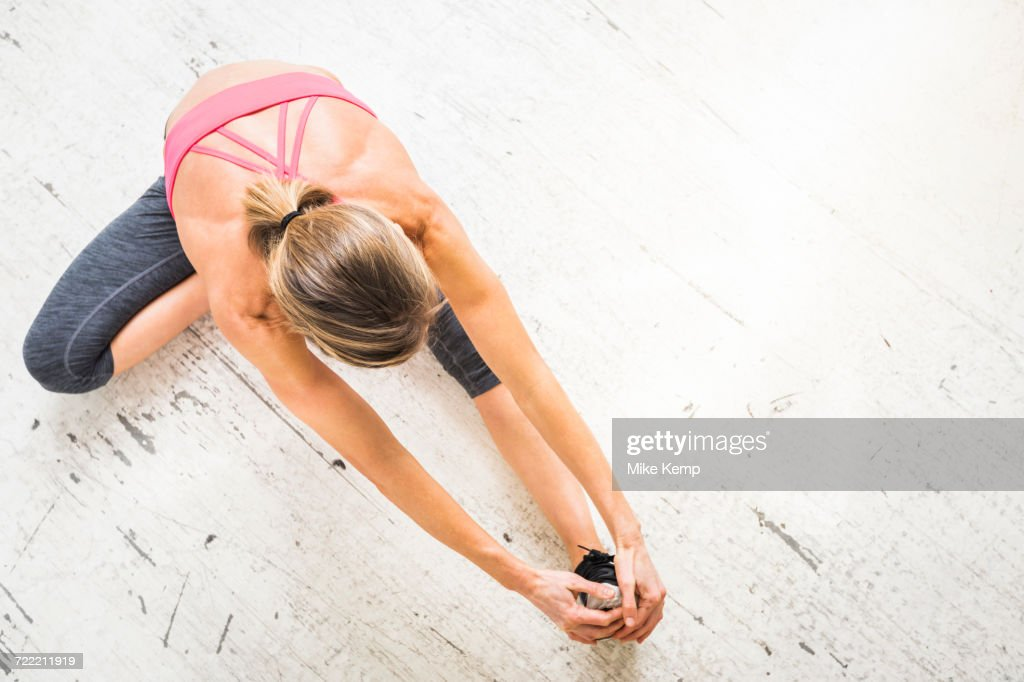 Woman sitting on wooden floor stretching leg : Stock Photo