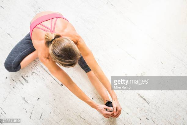 Woman sitting on wooden floor stretching leg