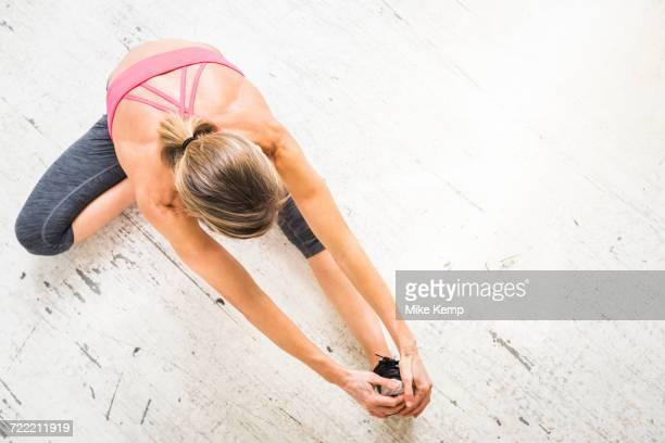 woman sitting on wooden floor stretching leg - perna humana - fotografias e filmes do acervo