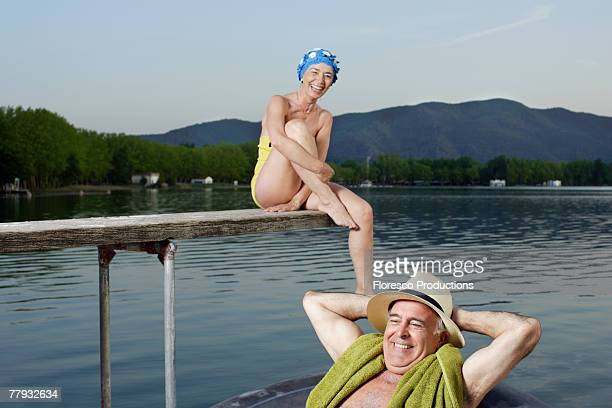 Woman sitting on wooden plank over lake with man in innertube floating by