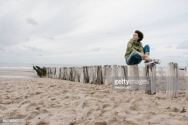 Woman sitting on wooden stake on the beach