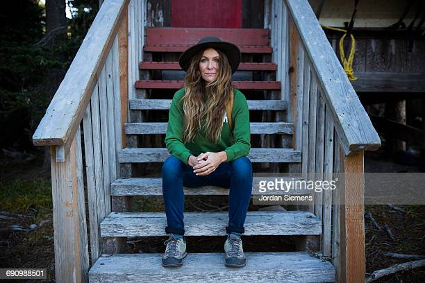 A woman sitting on wooden steps.