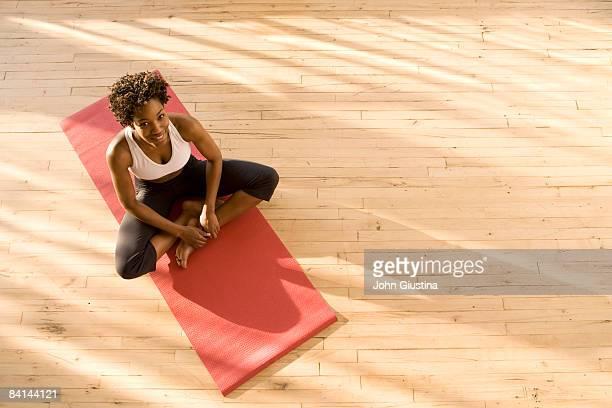 woman sitting on yoga mat. - エクササイズマット ストックフォトと画像